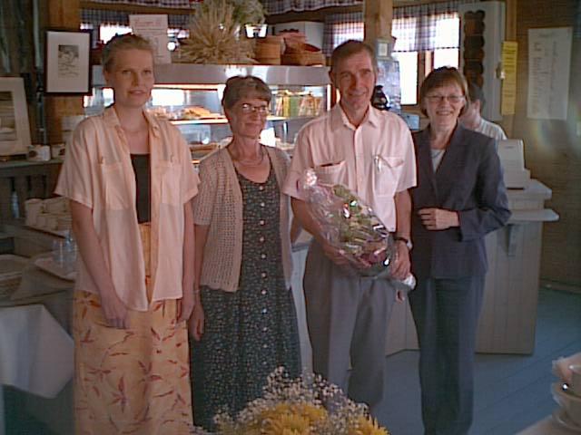 Anita Räsänen (vas.) ja Marja-Liisa Konkola (oik.) ojensivat suvun puolesta 60 -vuotialle Pentti Hätiselle onnittelukukat Tuusniemen vanhalla myllyllä 2002. Kuvassa myös Tuula Hätinen.